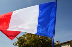 French flag in the wind on a sunny day. With blue sky background stock images
