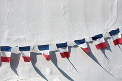 French Flags. Seven small french flags hanging on a line across a white plaster wall in bright sunlight Royalty Free Stock Images