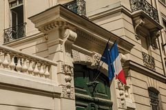 French flags above wooden door on an old building in a cloudy day at Paris. Royalty Free Stock Photo
