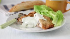 French food. French deep fried cordon bleu with salad on white plate stock footage