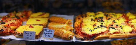 French Food For Sale at Antibes Market, Provence France. Including Sausage rolls, pizza, cheese on toast, tarts, slices and  pies Stock Photos