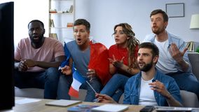 French friends watching match on tv at home, supporting favorite football team stock images