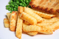 French Fries. Crinkle-cut french fried potatoes with steak pie and garden peas Royalty Free Stock Image