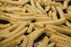 French fries. Raw or half raw french fries on black desk Stock Photo
