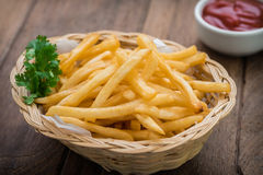 French fries in basket and ketchup on wooden table Royalty Free Stock Photos