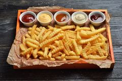 French fries on big wooden tray with sauces Royalty Free Stock Photo