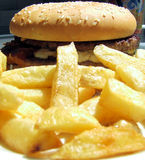 French fries and burger. Portion of homemade french fries with hamburger Stock Photography