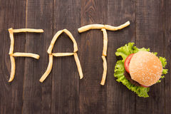 French fries with burger forming word fat on wooden background Royalty Free Stock Photos