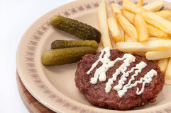 French fries, burger with mayonnaise and pickles served on a pla Royalty Free Stock Image