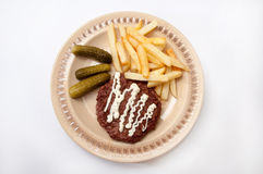 French fries, burger with mayonnaise and pickles served on a pla Stock Photos