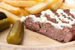 French fries, burger with mayonnaise and pickles served on a pla Royalty Free Stock Images