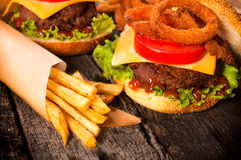 French fries and cheesburger. Juicy cheeseburger with onion rings and french fries Stock Photos