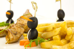 French fries and chicken kebabs Stock Photos