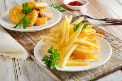 French fries and chicken nuggets on   wooden table Royalty Free Stock Photos