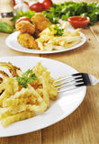 French fries and chicken on the plate on the wooden table Stock Photography