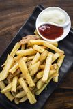 French fries chips with diping sauces on wooden table Stock Photos