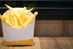 French fries. Close up french fries in a white paper on the brown table Royalty Free Stock Photos