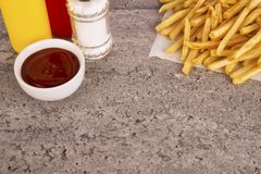 French fries on a concrete texture table. Copy space for your text. French fries on a concrete texture table. Fast food restaurant concept. Copy space for your royalty free stock photos
