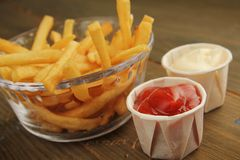 French fries with condiment. French fries with a choice of ketchup and mayonnaise Stock Image