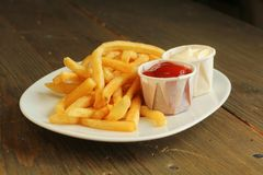 French fries with condiment. French fries in a white plate with a choice of ketchup and mayonnaise Stock Photography