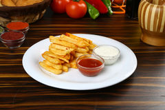 French fries. Crunchy French Fries with sauces on plate Royalty Free Stock Photos