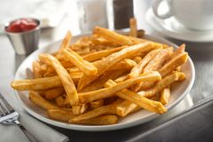 French Fries in a Diner. A plate of delicious crispy french fries served in a diner on a stainless steel countertop Stock Photography