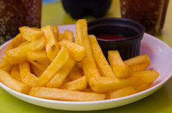 French fries in dise on table. Fried potatoes with spicy sauce Stock Images
