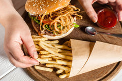 French fries eating top view. Hand taking fried potato from paper pack on tray with burger. American traditional cuisine, lunch time, fast junk food concept Stock Images