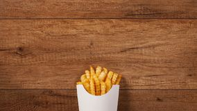 French fries falling into and pouring out of paper holder on brown wooden table stock footage