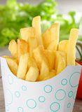 French Fries in Fast Food container. On the wooden table Stock Image