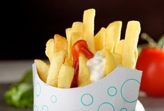 French Fries in Fast Food container. On the wooden table Royalty Free Stock Photography