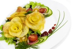 French fries in the form of a rose on a plate with a salad on wh Stock Photo