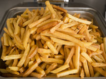 French fries fresh cooked. Restaurant deep fryer, metal container with lots of potatoes fried. Street food, fast food. Stock Photo