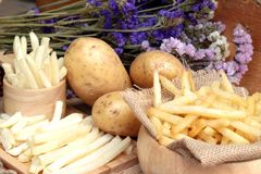 French fries and fresh potatoes sliced.  Stock Photos