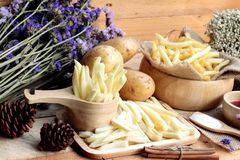 French fries and fresh potatoes sliced.  Royalty Free Stock Photos