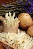 French fries and fresh potatoes sliced.  Royalty Free Stock Images