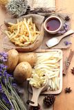 French fries and fresh sliced potatoes with ketchup. French fries and fresh sliced potatoes with ketchup Royalty Free Stock Photography