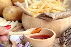 French fries and fresh sliced potatoes with ketchup. Stock Photos