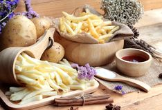 French fries and fresh sliced potatoes with ketchup. Stock Image