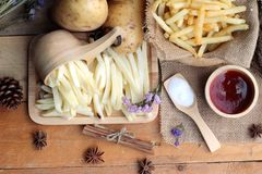 French fries and fresh sliced potatoes with ketchup. Stock Photography