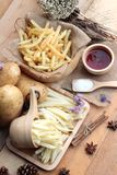 French fries and fresh sliced potatoes with ketchup. French fries and fresh sliced potatoes with ketchup Royalty Free Stock Photos