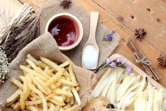 French fries and fresh sliced potatoes with ketchup. French fries and fresh sliced potatoes with ketchup Royalty Free Stock Image