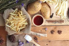 French fries and fresh sliced potatoes with ketchup. Stock Images