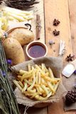 French fries and fresh sliced potatoes with ketchup. Royalty Free Stock Photos