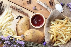 French fries and fresh sliced potatoes with ketchup. French fries and fresh sliced potatoes with ketchup Stock Image