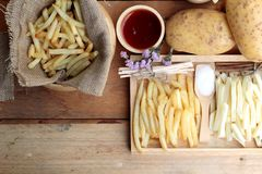 French fries and fresh sliced potatoes with ketchup. Royalty Free Stock Images