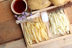 French fries and fresh sliced potatoes with ketchup. Royalty Free Stock Image