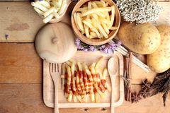 French fries and fresh sliced potatoes with ketchup. Stock Photo