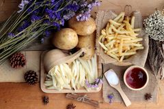 French fries and fresh sliced potatoes with ketchup. French fries and fresh sliced potatoes with ketchup Stock Photography