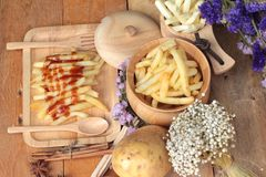 French fries and fresh sliced potatoes with ketchup. French fries and fresh sliced potatoes with ketchup Royalty Free Stock Images